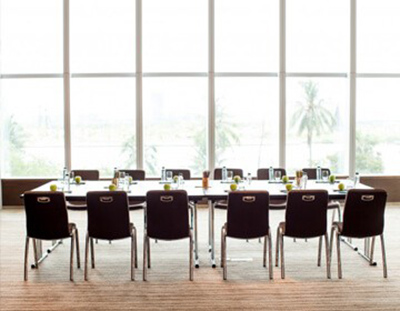 A long conference table with a full wall of bright, clean windows