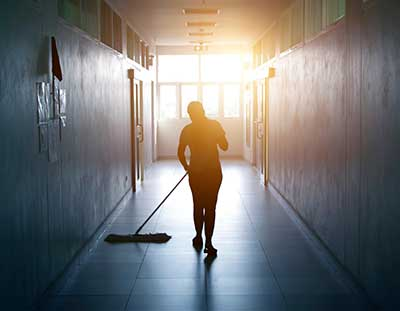A cleaner walks down a stark hallway pushing a broom