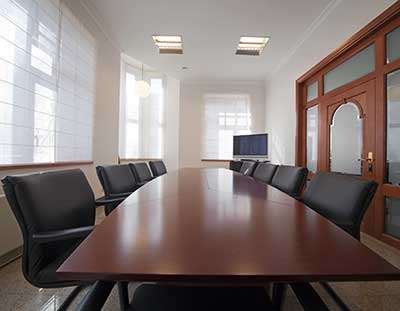 A shiny wooden conference room table surrounded by comfortable black chairs