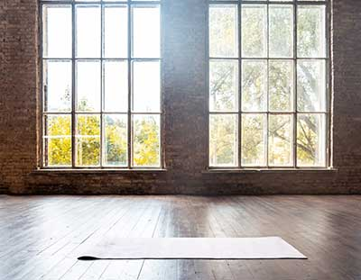 A spotless yoga studio with wood floors, large windows, and brick walls